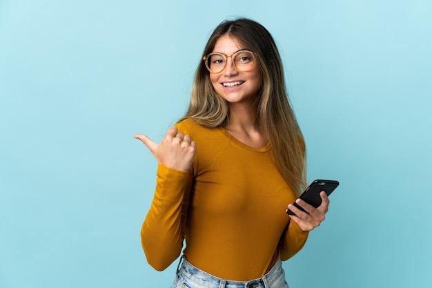 製品を提示するために側面を指している青で隔離の携帯電話を使用して若い白人女性