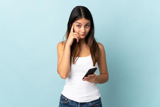 Молодая кавказская женщина с помощью мобильного телефона изолирована на синем, думая об идее