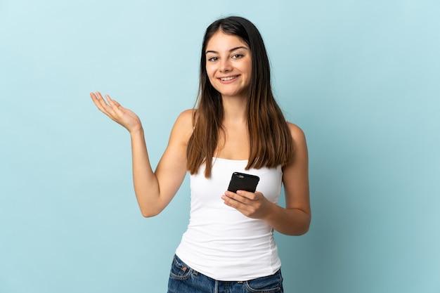 青い壁に隔離された携帯電話を使用して、来るように誘うために手を横に伸ばしている若い白人女性