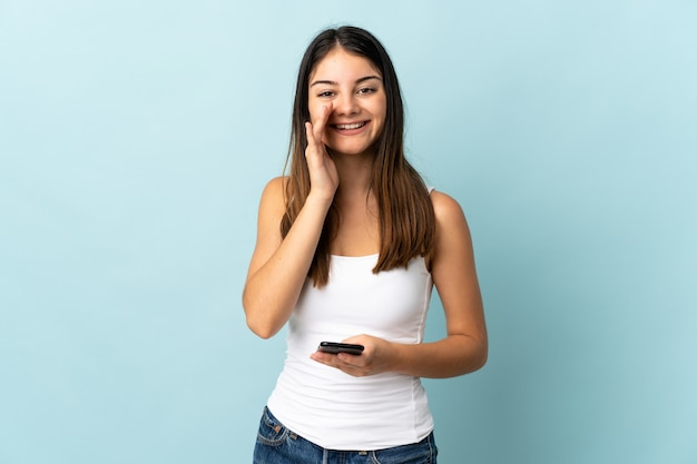 口を大きく開いて叫んで青い壁に分離された携帯電話を使用して若い白人女性