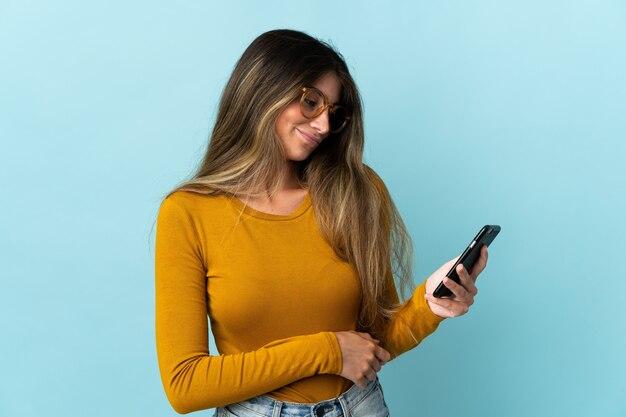 슬픈 표정으로 파란색에 고립 된 휴대 전화를 사용하는 젊은 백인 여자