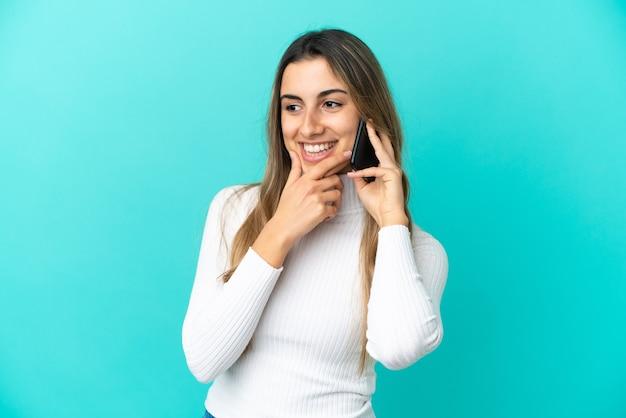 Молодая кавказская женщина с помощью мобильного телефона изолирована, глядя в сторону и улыбаясь