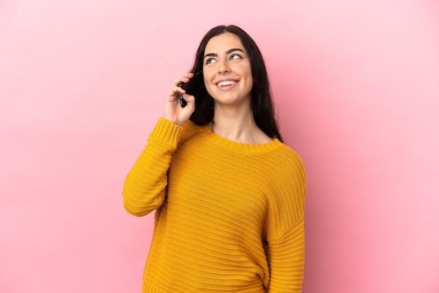 찾는 동안 아이디어를 생각 분홍색 배경에 고립 된 휴대 전화를 사용하는 젊은 백인 여자