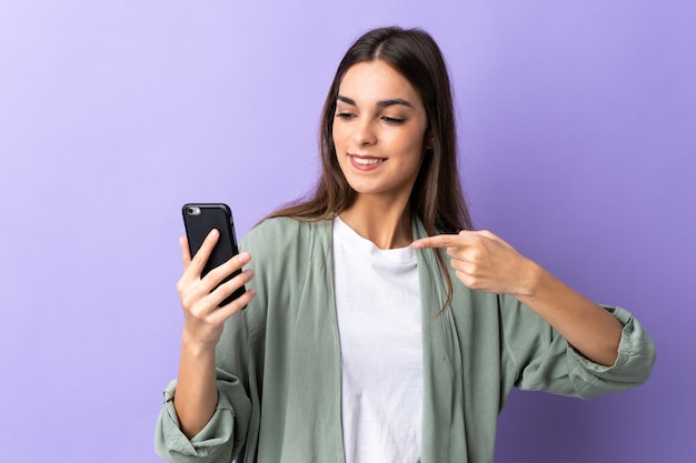 Молодая кавказская женщина с помощью мобильного телефона изолирована на фиолетовом фоне и указывает на нее
