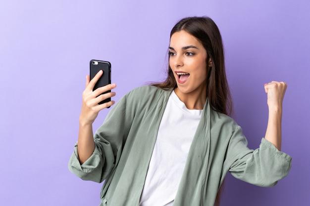 Молодая кавказская женщина с помощью мобильного телефона на фиолетовом фоне празднует победу