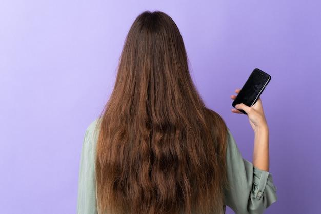 Молодая кавказская женщина с помощью мобильного телефона изолирована на фиолетовом фоне в заднем положении