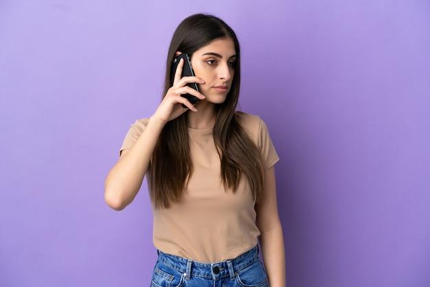 Молодая кавказская женщина с помощью мобильного телефона изолирована на фиолетовом фоне, глядя в сторону