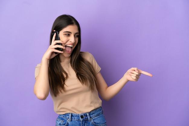 Молодая кавказская женщина с помощью мобильного телефона изолирована на фиолетовом фоне, указывая пальцем в сторону и представляя продукт