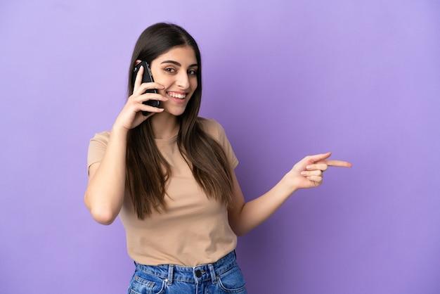 보라색 배경에서 손가락을 옆으로 가리키는 휴대전화를 사용하는 젊은 백인 여성