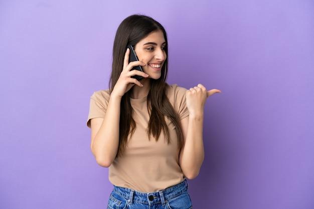 제품을 제시하기 위해 측면을 가리키는 보라색 배경에 격리된 휴대 전화를 사용하는 젊은 백인 여성