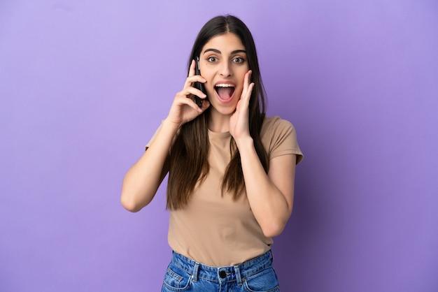 驚きとショックを受けた表情で紫色の背景に分離された携帯電話を使用して若い白人女性