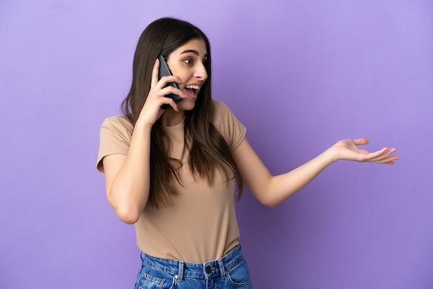 보라색 배경에 격리된 휴대전화를 사용하는 젊은 백인 여성, 옆을 바라보면서 놀란 표정