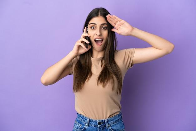 깜짝 표정으로 보라색 배경에 고립 된 휴대 전화를 사용 하는 젊은 백인 여자