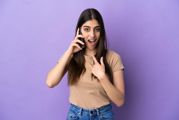驚きの表情で紫色の背景に分離された携帯電話を使用して若い白人女性