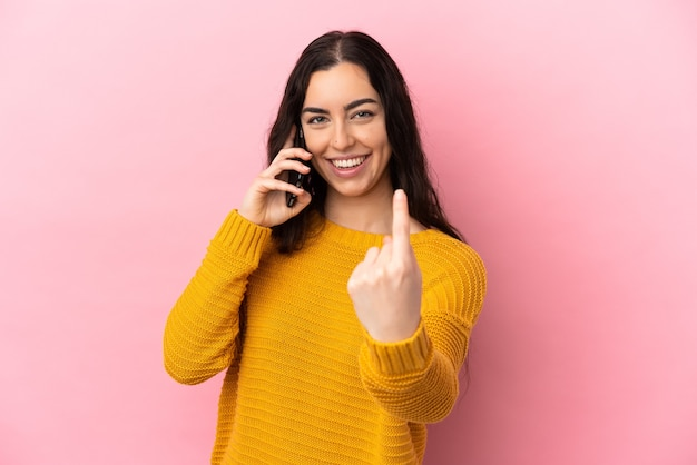 Young caucasian woman using mobile phone isolated on pink background doing coming gesture