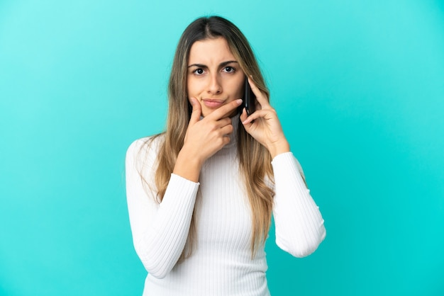Young caucasian woman using mobile phone isolated on thinking