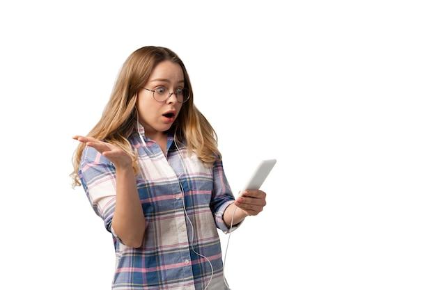 흰색 스튜디오 벽에 격리된 스마트폰, 장치, 가제트를 사용하는 젊은 백인 여성.