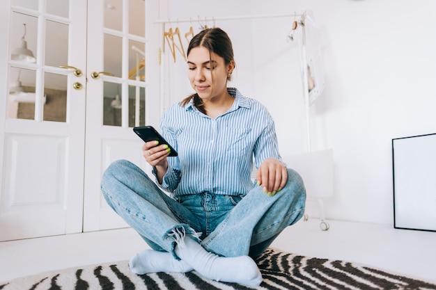 젊은 백인 여자 스마트 폰을 사용하여 흰색 옷장 방 바닥에 앉아 인터넷 검색 및 온라인 쇼핑.