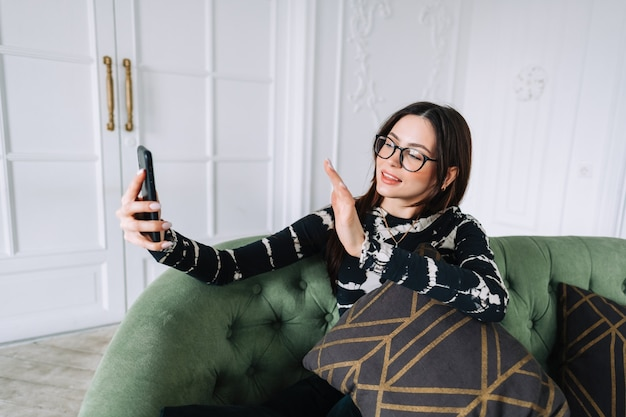 Молодая кавказская женщина с помощью видеозвонка на мобильном телефоне дома, ткачество.
