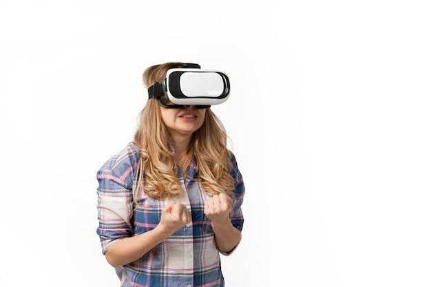 Vrヘッドセットデバイス、白いスタジオの壁に隔離されたガジェットを使用している若い白人女性。