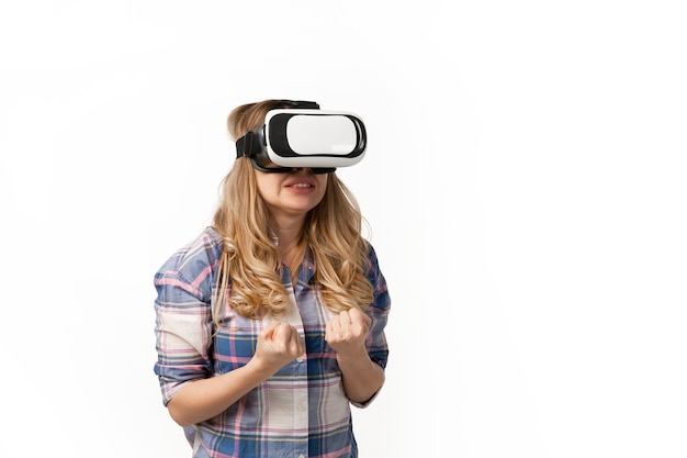 Young caucasian woman using vr-headset devices, gadgets isolated on white studio wall.