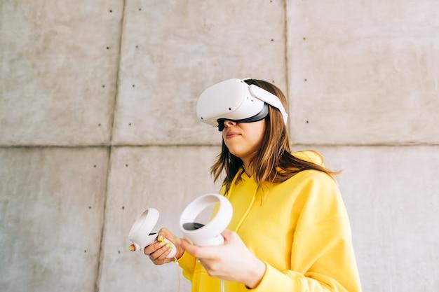 Молодая кавказская женщина с помощью гарнитуры vr, держа контроллеры и глядя в виртуальной реальности.