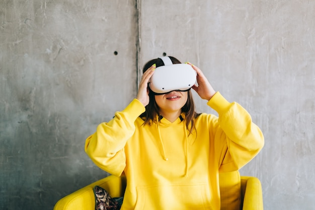 Молодая кавказская женщина с помощью гарнитуры vr, трогательно очки и глядя в виртуальной реальности.