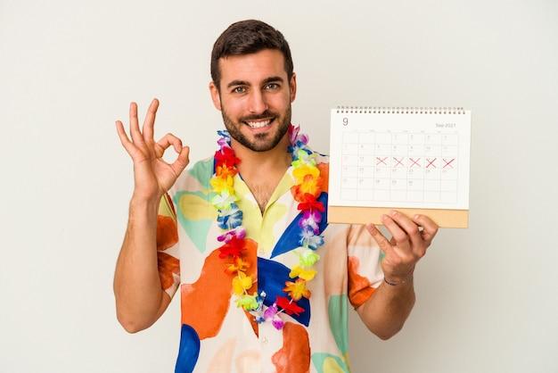 白い背景に分離されたカレンダーを持って休暇を待っている若い白人女性は陽気で自信を持って大丈夫なジェスチャーを示しています。