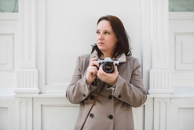 Молодая кавказская женщина на белой стене с ее старой камерой.