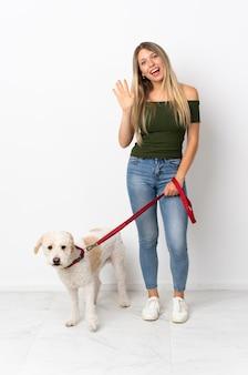 Молодая кавказская женщина гуляет с собакой на белом салютует рукой с счастливым выражением лица