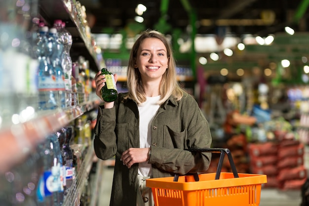 若い白人女性は、バスケットを手にスーパーマーケットの列の間を歩きます。グッズセクションでの女性の買い物、ブラウジング。通路がたくさんある大きな店。食料品店で商品を選ぶ