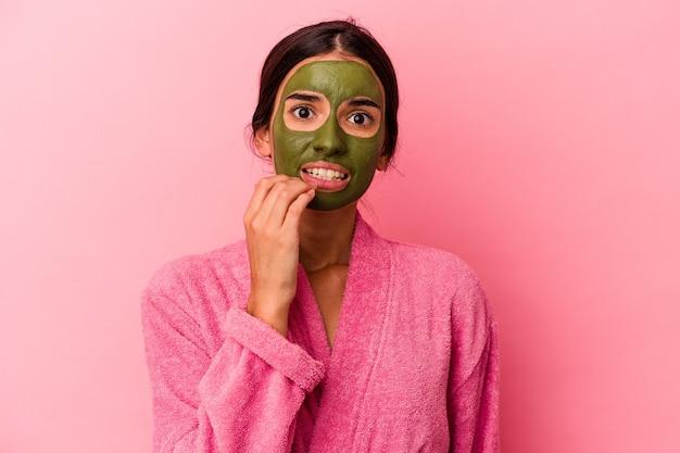 분홍색 배경에 격리된 목욕 가운과 얼굴 마스크를 쓴 백인 젊은 여성은 손톱을 물어뜯고 긴장하고 매우 불안해합니다.