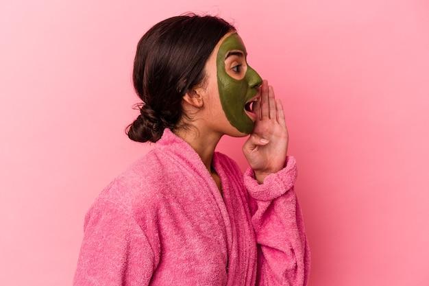 Молодая кавказская женщина в халате и маске для лица, изолированных на розовом фоне, кричит и держит ладонь возле открытого рта.