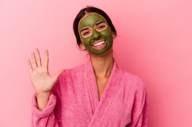 ピンクの背景に分離されたバスローブと顔のマスクを身に着けている若い白人女性は、指で5番を示して陽気に笑っています。