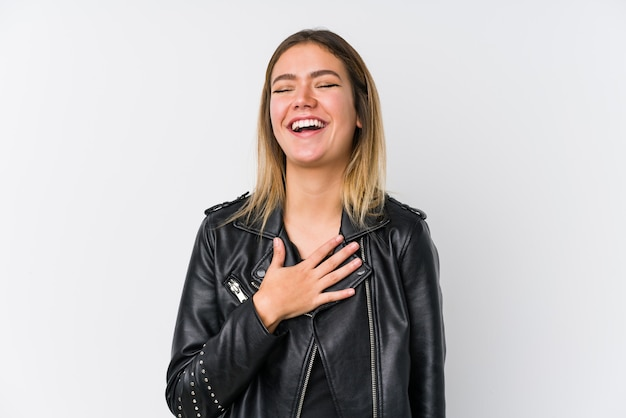 黒い革のジャケットを着た若い白人女性は、胸に手を置いて大声で笑います。