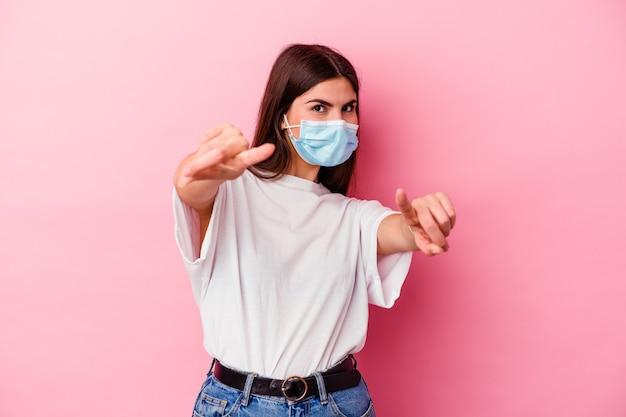 Молодая кавказская женщина в маске от вируса изолирована на розовой стене с веселыми улыбками, указывающими вперед
