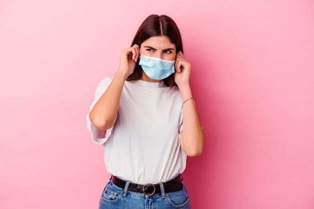 손으로 귀를 덮고 분홍색 벽에 고립 된 바이러스 마스크를 쓰고 젊은 백인 여자