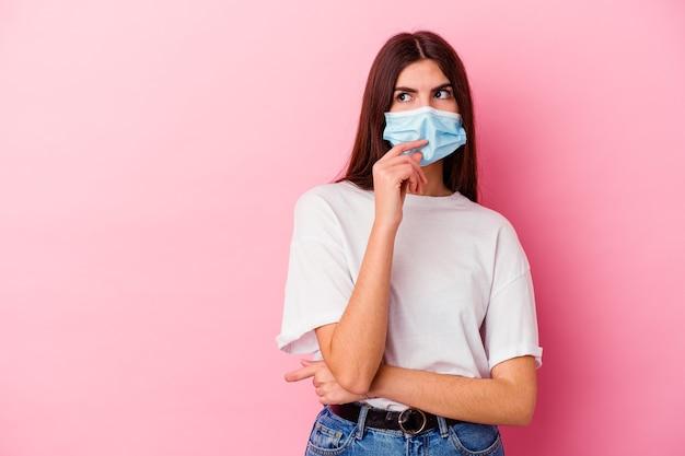 분홍색 벽에 고립 된 바이러스 마스크를 쓰고 젊은 백인 여자는 복사 공간을보고 뭔가에 대해 생각을 편안하게