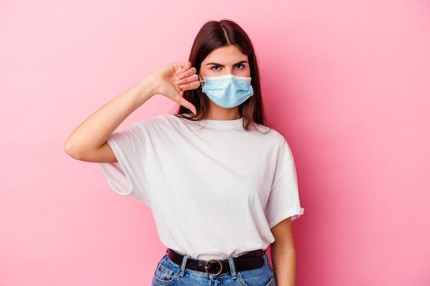 Молодая кавказская женщина в маске от вируса, изолированной на розовой стене, показывает жест неприязни, пальцы вниз. концепция несогласия.