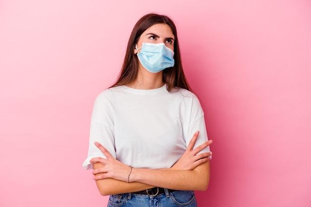 Молодая кавказская женщина в маске от вируса, изолированной на розовой стене, устала от повторяющейся задачи.