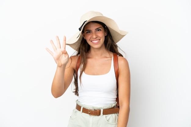 Молодая кавказская женщина в памеле в летние каникулы, изолированные на белом фоне, счастлива и считает четыре пальцами