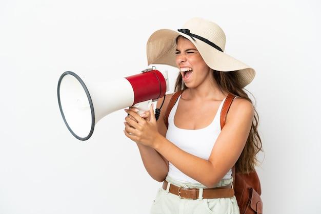 Молодая кавказская женщина в памеле в летние каникулы, изолированные на белом фоне, кричит в мегафон