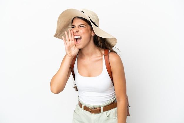 Молодая кавказская женщина в памеле на летних каникулах изолирована на белом фоне и кричит с широко открытым ртом