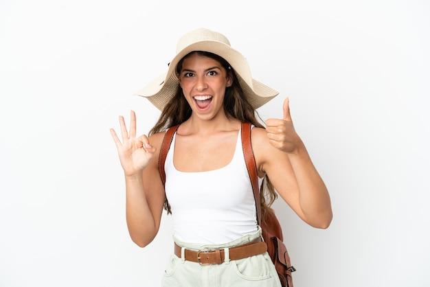 Молодая кавказская женщина в памеле в летние каникулы изолирована на белом фоне, показывая знак ок и жест пальца вверх