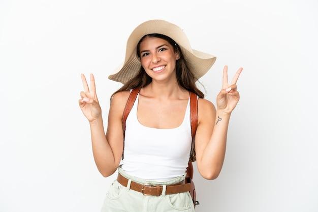 Молодая кавказская женщина в памеле на летних каникулах изолирована на белом фоне, показывая знак победы обеими руками
