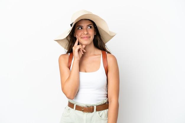 Молодая кавказская женщина в памеле в летние каникулы изолирована на белом фоне, думая об идее, глядя вверх