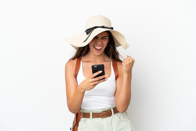 Молодая кавказская женщина в памеле в летние каникулы изолирована на белом фоне с телефоном в победной позиции