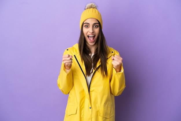 우승자 위치에서 승리를 축하하는 보라색 배경에 고립 된 방수 코트를 입고 젊은 백인 여자