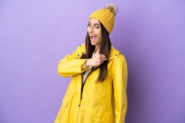 勝利を祝う紫色の背景に分離された防雨コートを着ている若い白人女性