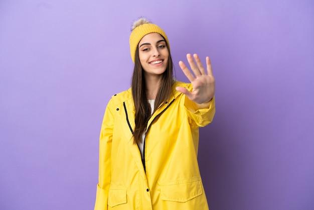 Молодая кавказская женщина в непромокаемом пальто на фиолетовом фоне считает пять пальцами